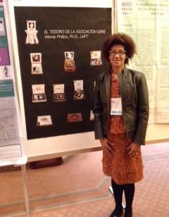 "Wendy Phillips stands next to a sign that reads ""El Tesoro de la Asocicion Libre"""