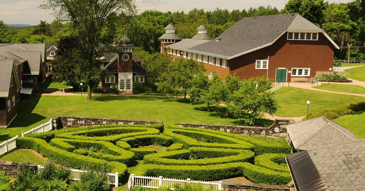 Birds-eye view of green grass and red historic structures of the Goddard Greatwood campus